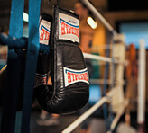 Boxing gloves hanging on ropes of boxing ring