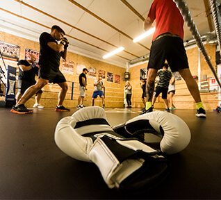 White boxing gloves on mat next to boxers training