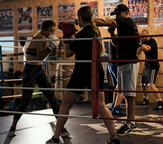 Two fighters getting trained in ring by boxing coach